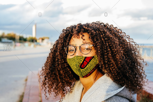 Ethnic female in fabric mask and glasses looking at camera while resting on embankment during pandemic in city