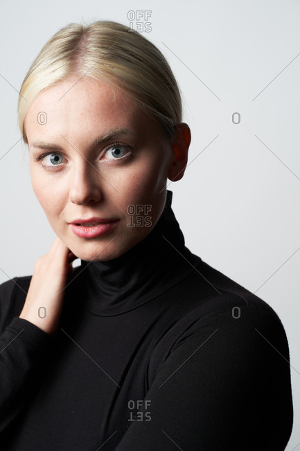 Blonde young female in casual apparel in studio looking at camera