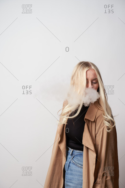 Tranquil female in stylish outfit standing in studio and smoking vape while looking down