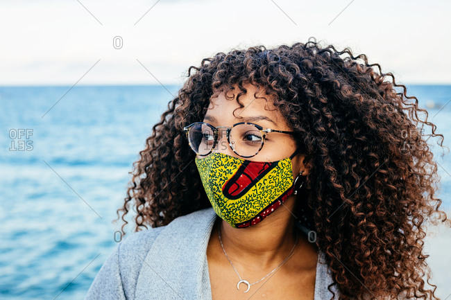 Ethnic female in fabric mask and glasses looking away while resting on embankment during pandemic in city