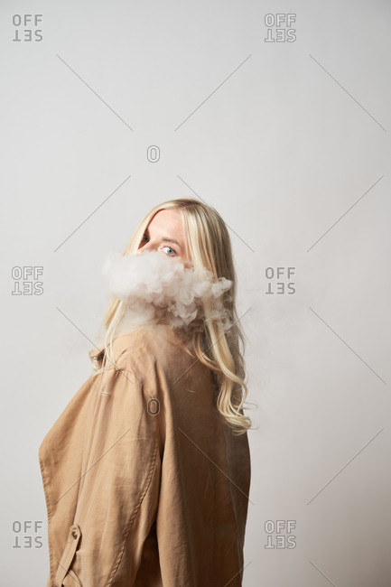 Side view of tranquil female in stylish outfit standing in studio and smoking vape looking at camera