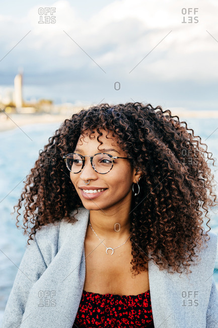 Happy African American female smiling and looking away while standing on quay near sea