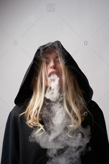 Rebellious young female in black hoodie smoking e cigarette and exhaling steam while looking at camera on dark gray background