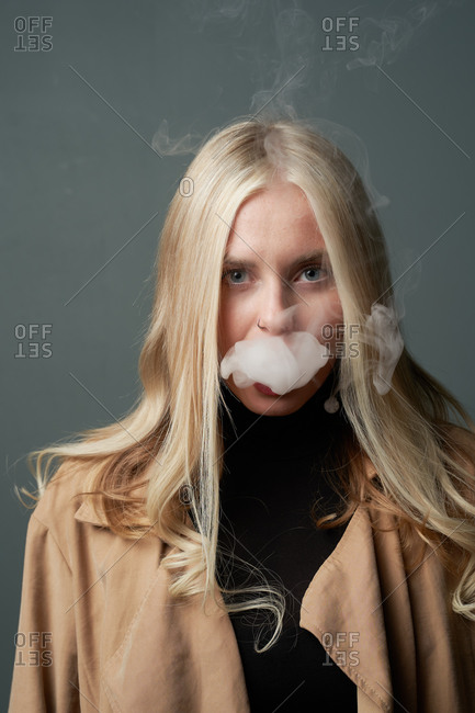Tranquil female in stylish outfit standing in studio and smoking vape looking at camera