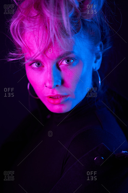 Confident young blonde female in black outfit and hoop earrings with face illuminated by purple neon light looking at camera in dark studio