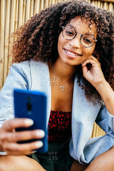 Happy ethnic female in trendy outfit smiling and browsing smartphone while sitting on wooden floor near bamboo wall