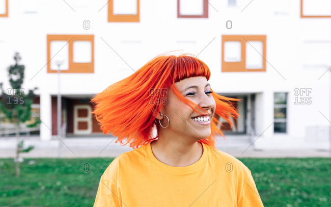 Excited adult woman laughing and shaking ginger dyed hair outside modern building on street