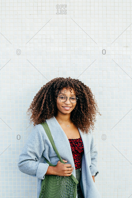 Friendly black female with cotton bag smiling and looking at camera while leaning on tiled wall on city street