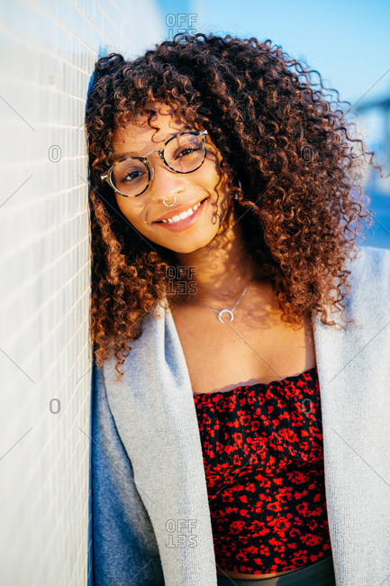 Friendly black female smiling and looking at camera while leaning on tiled wall on city street