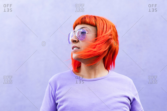 Adult female with vibrant red dyed hair and in stylish sunglasses looking away against violet wall on street