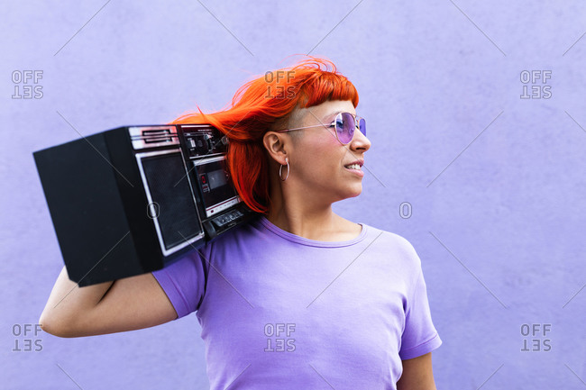 Trendy adult woman with bright ginger dyed hair carrying boom box on shoulder and looking away while listening to music against violet wall