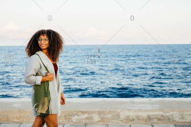 Happy African American female with fabric bag smiling and looking away while walking on quay near sea