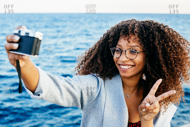 Delighted black woman with curly hair gesturing V sign and smiling while taking selfie near rippling sea on weekend day
