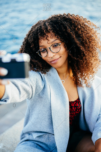 Delighted black woman with curly hair smiling while taking selfie near rippling sea on weekend day