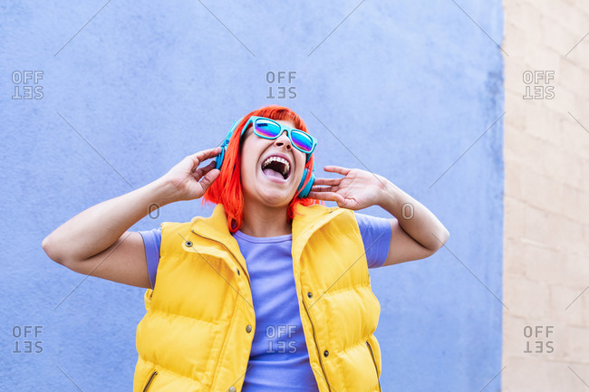 Happy stylish adult female with ginger dyed hair listening to music in headphones and singing along against violet wall in city