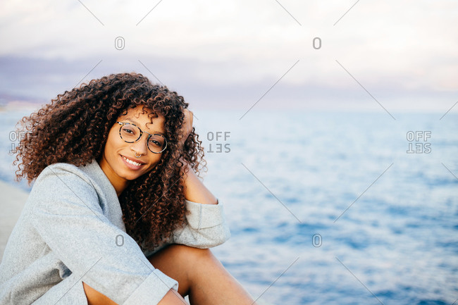 Happy African American female looking at camera while standing on quay near sea