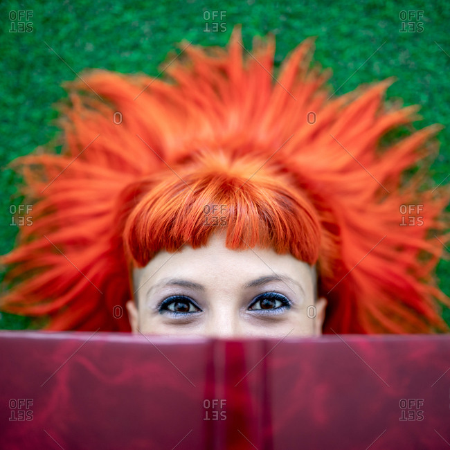 Top view of adult female with vivid ginger dyed hair peeking from behind book and looking at camera while relaxing on lawn