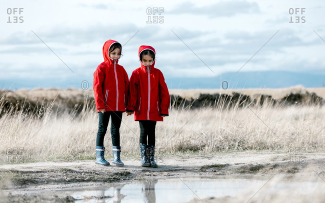 Carefree kids in raincoats and rubber boots in puddle on sunny day in countryside
