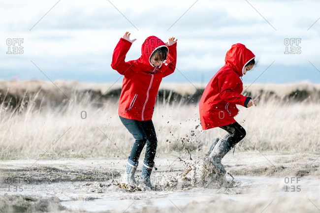 Carefree kids in raincoats and rubber boots splashing water in puddle while having fun and laughing on sunny day in countryside