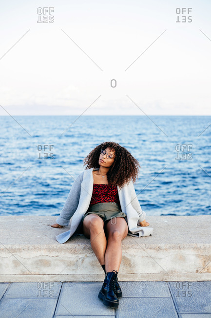 Happy African American female looking away while standing on quay near sea