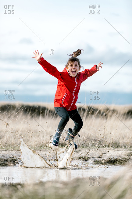 Carefree kid in raincoats and rubber boots splashing water in puddle while having fun and laughing on sunny day in countryside