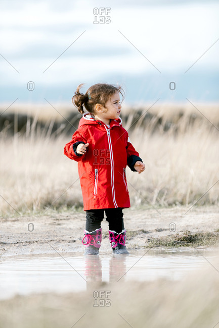 Carefree kid in raincoats and rubber boots in puddle on sunny day in countryside