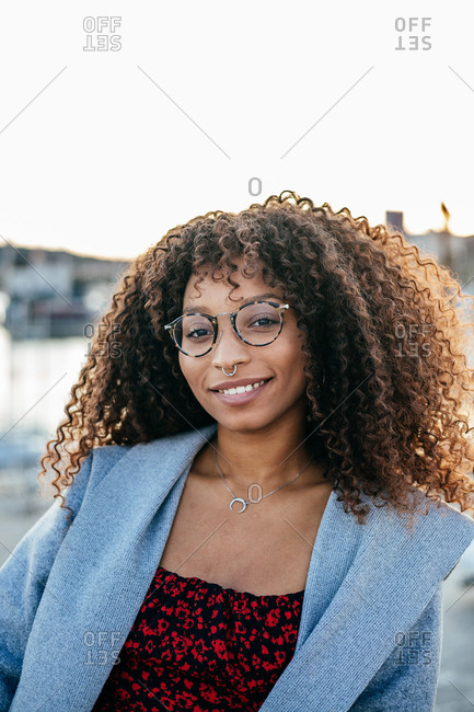 Happy African American female smiling and looking at camera while standing on quay near sea