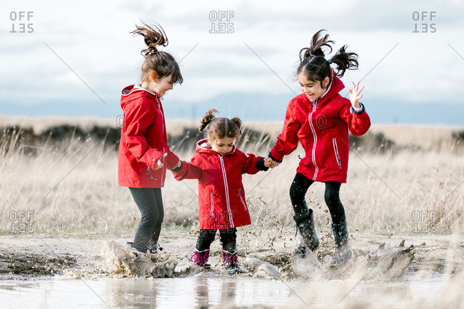 Delighted sisters holding hands and jumping in dirty puddle while having fun in countryside