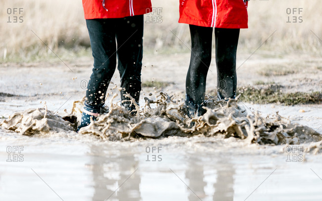 Unrecognizable carefree kids in raincoats and rubber boots splashing water in puddle while having fun on sunny day in countryside
