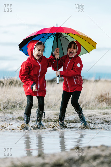 Excited sisters with colorful umbrella and in rubber boots playing in puddle while splashing water and having fun