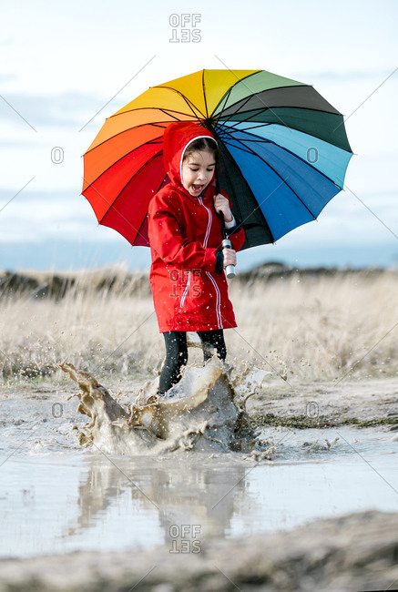 Excited little girl with colorful umbrella and in rubber boots playing in puddle while splashing water and having fun