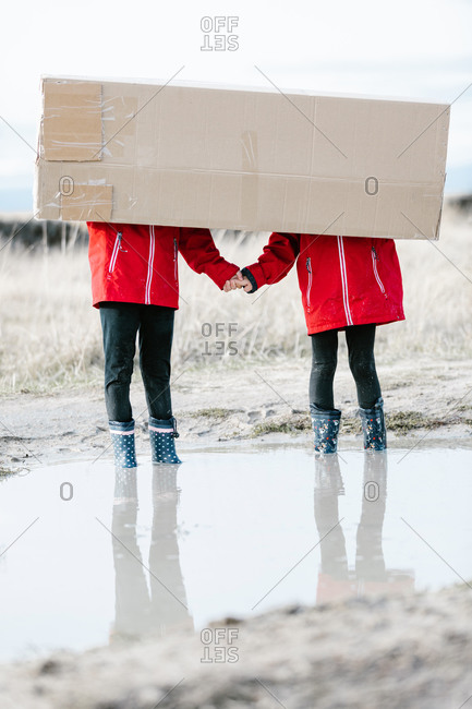Anonymous children in rubber boots and raincoats standing in puddle and hiding behind cardboard package while having fun during weekend
