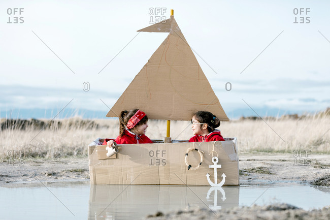 Playful children sitting in handmade cardboard boat in puddle and looking through spyglass while having fun at weekend together