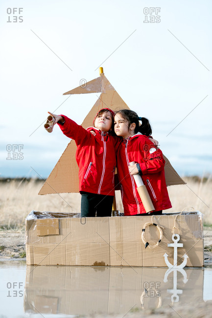 Side view of cheerful kids with handmade spyglass standing in handmade cardboard boat and playing