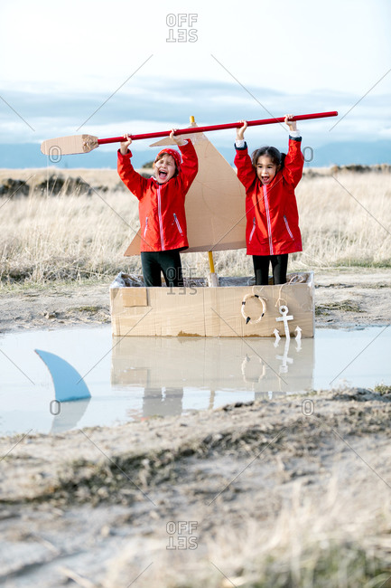 Optimistic children standing in carton boat with paddle above heads while having fun and enjoying game