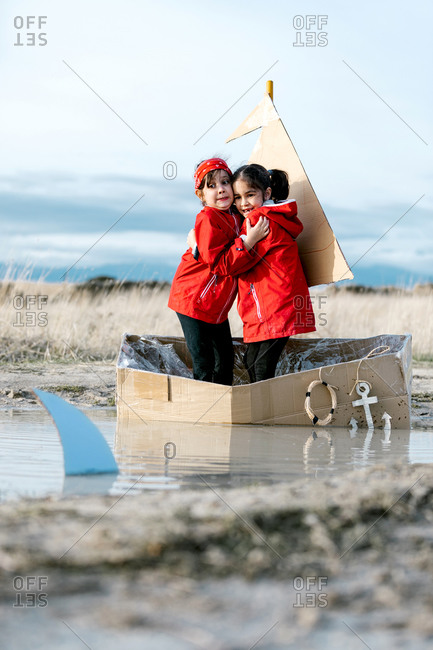 Frightened playful kids scared of carton shark hugging in handmade cardboard boat and playing in countryside