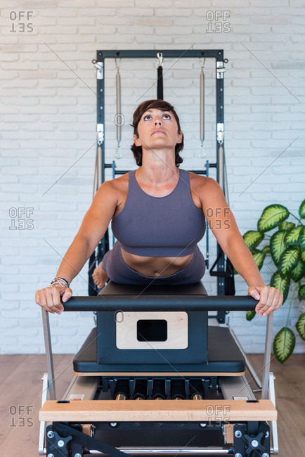 Fit adult woman doing Swan exercise and looking up while stretching body on Pilates reformer in gym
