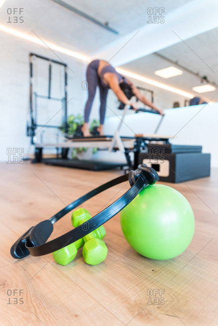 Pilates ring placed on green ball and dumbbells on floor near woman exercising on reformer in gym