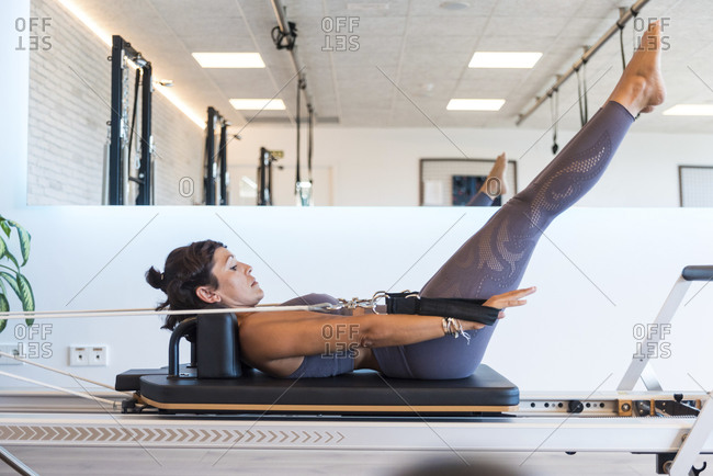 Side view of slim adult woman in sportswear doing Hundred exercise with resistance bands on reformer during Pilates workout in gym