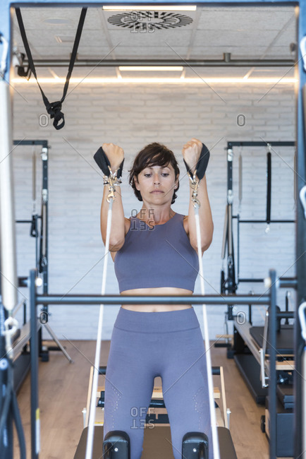 Fit woman in sportswear pulling resistance ropes and doing Kneeling Lean Back exercise on reformer during Pilates workout in modern gym