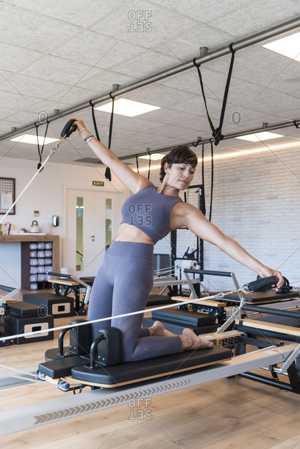 Fit adult female doing Kneeling Lean Back exercise with outstretched arms on reformer during Pilates workout in gym