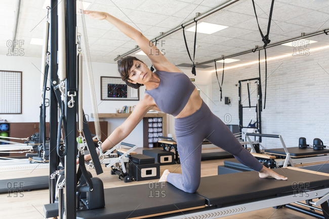 Fit adult woman doing Gate pose on bench and stretching body during Pilates training in gym
