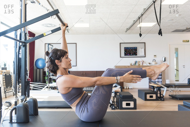 Side view of slim woman in sportswear grasping bar and doing Half Boat pose during Pilates training in gym