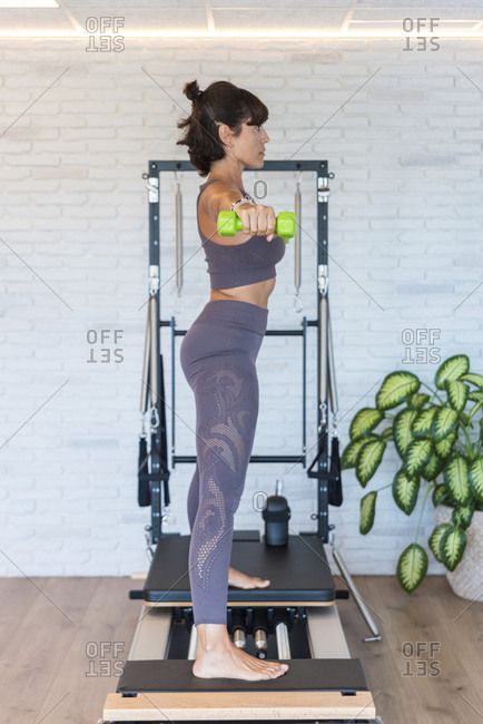 Side view of barefoot female stretching out arms with dumbbells while standing on reformer during Pilates workout in gym