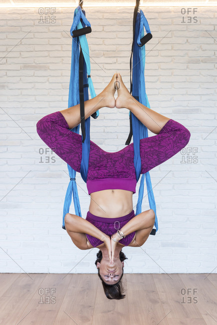 Adult female hanging on aerial silks in Inverted Butterfly pose and meditating with clasped hands and closed eyes against brick wall