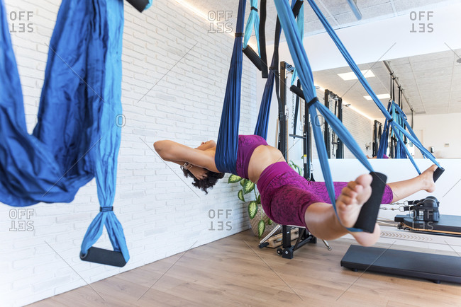 Barefoot female doing Boat pose on aerial silks during yoga lesson in modern gym