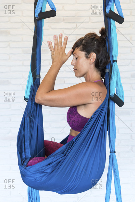 Side view of adult female with clasped hands and closed eyes sitting in hammock in Lotus pose and meditating while practicing aerial yoga against brick wall