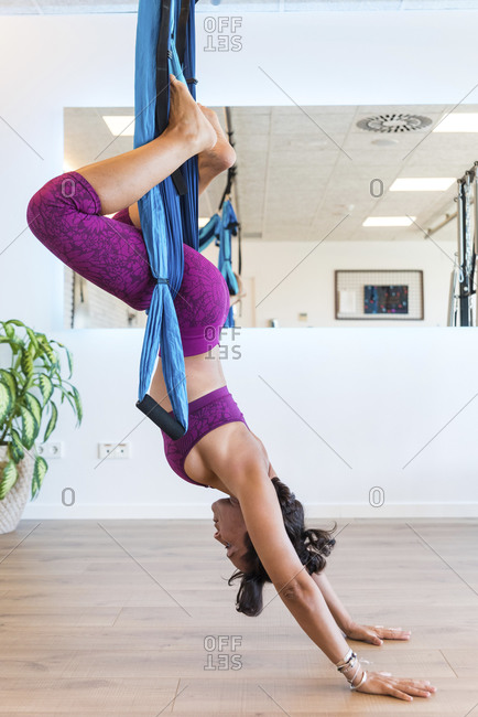 Side view of adult female doing Frog pose and stretching back on aerial ribbons while practicing yoga in studio