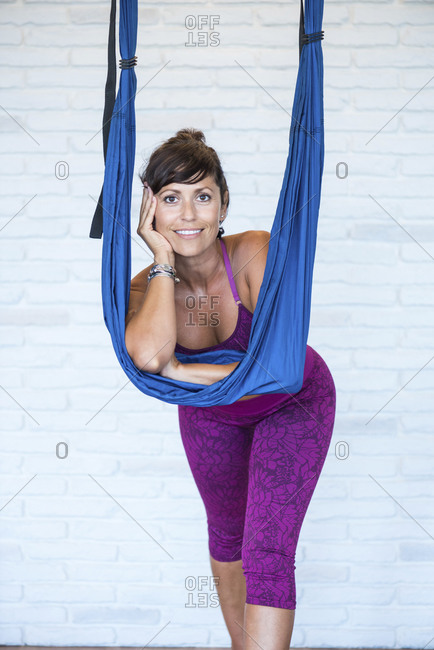 Cheerful adult female smiling and looking at camera while leaning on ribbon during break in aerial yoga lesson against brick wall
