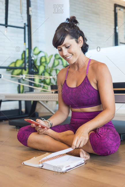 Happy female instructor sitting cross legged near Pilates reformer and dialing phone number from notebook on smartphone in gym